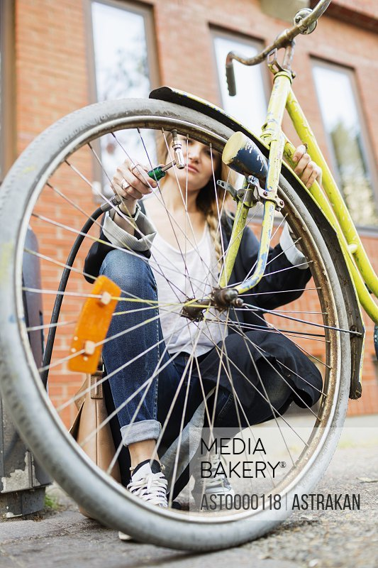 Woman inflating bicycle tire on sidewalk