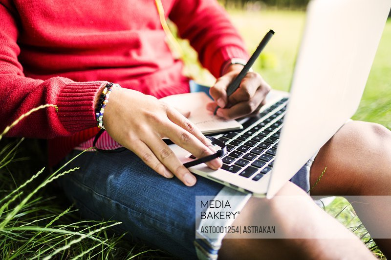 Midsection of university student writing in book while using laptop at park