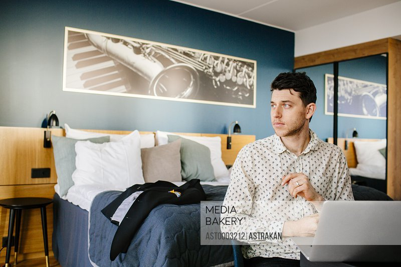 Businessman with laptop against bed at hotel room
