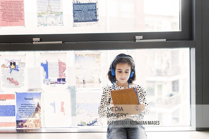 Girl (8-9) wearing headphones, using digital tablet