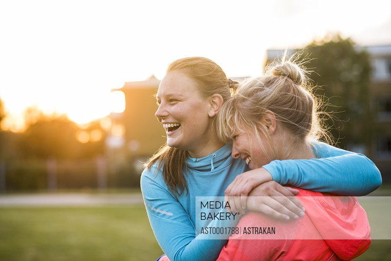 Cheerful sporty sisters embracing at park