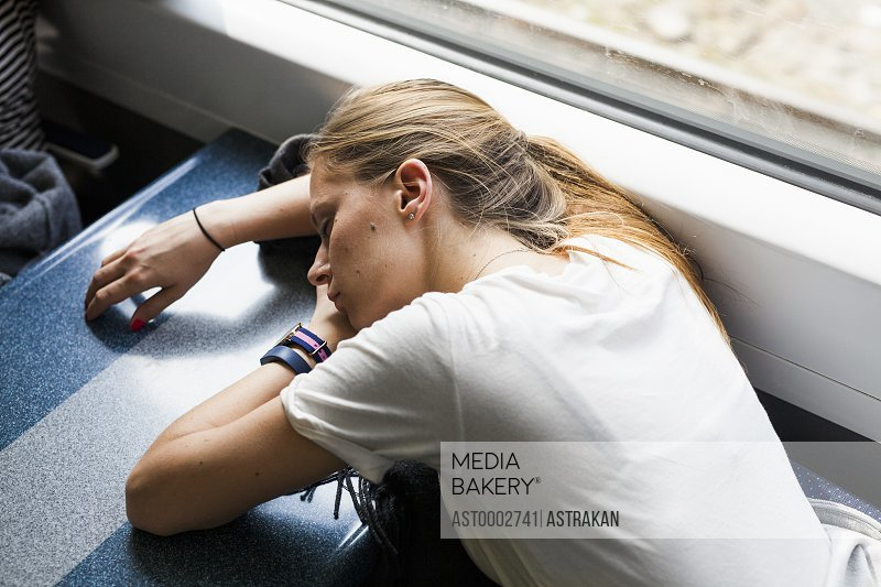 High angle view of tired businesswoman sleeping on table in train