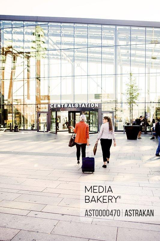 Rear view of businesswomen walking towards railroad station