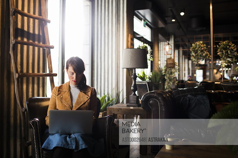Woman using laptop while sitting in cafe