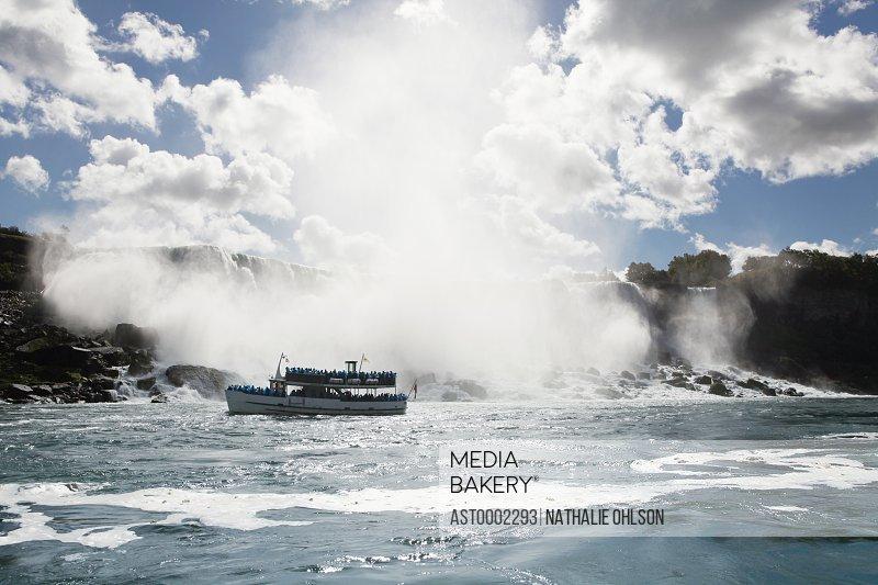 Ferry sailing by Niagara Falls against cloudy sky