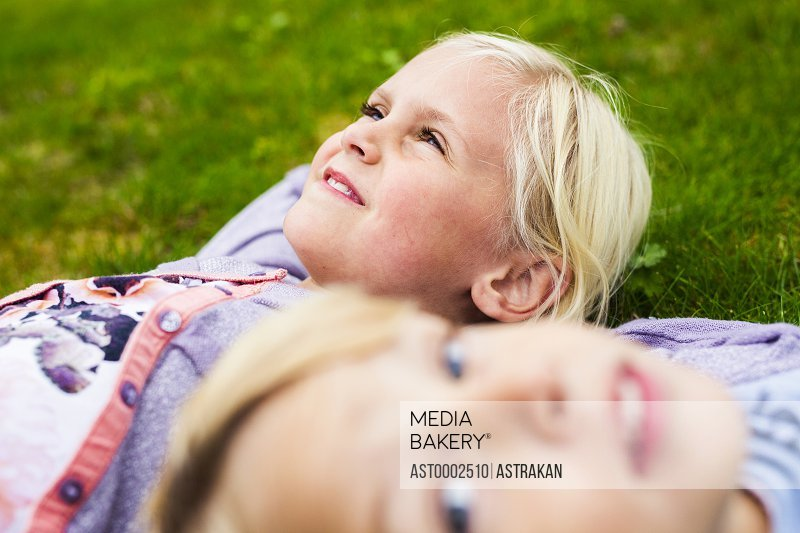 Thoughtful girl with brother lying on grass in yard