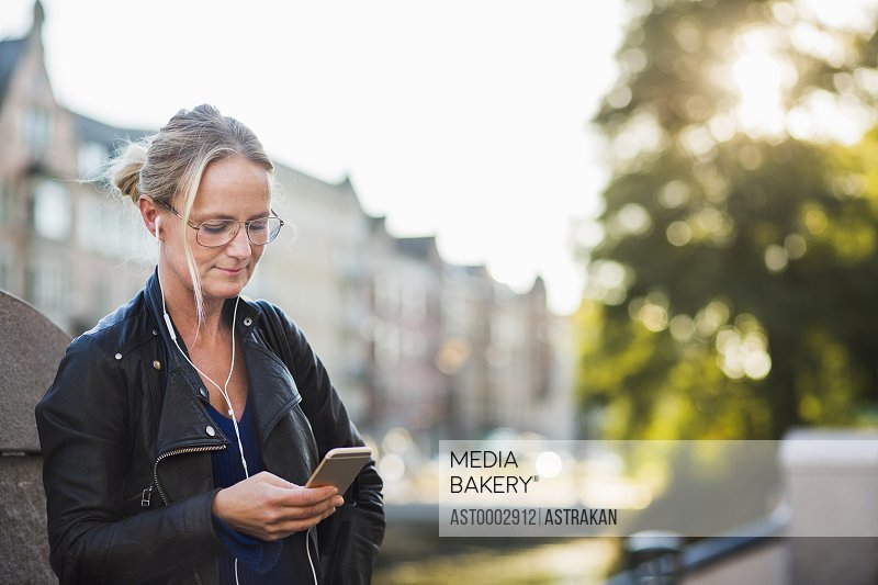 Mature woman with earphones looking at smart phone while standing at street