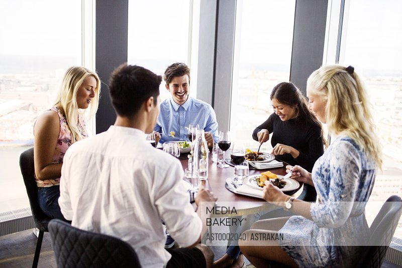 Happy friends having meal at Sky bar restaurant