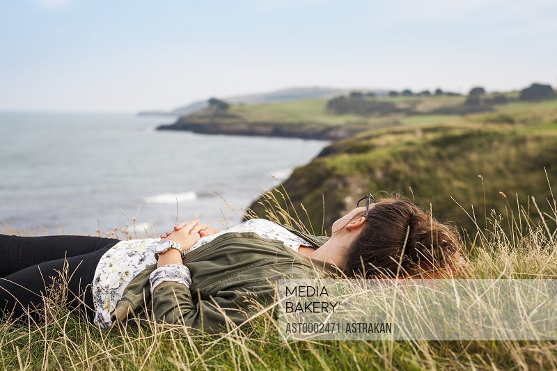 Side view of woman lying on grassy hill by sea