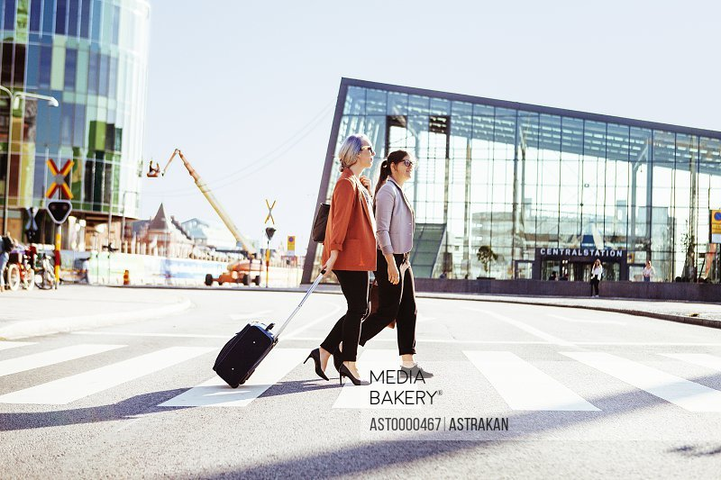 Side view of businesswomen walking outside railroad station