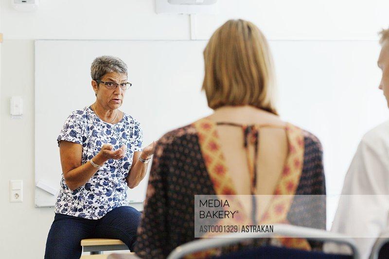 Mature teacher explaining students in classroom