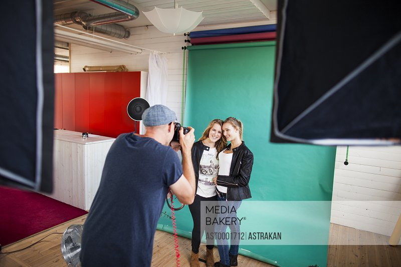 Rear view of photographer photographing fashion models in studio