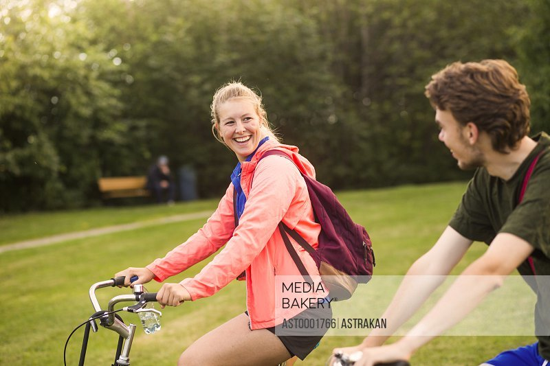 Happy sporty woman talking to male friend while cycling at park