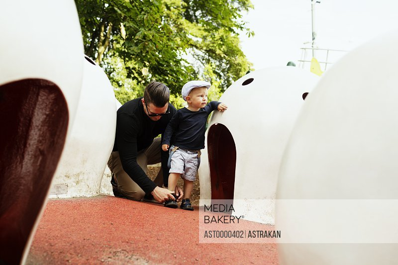 Father assisting son in wearing footwear by artificial igloos in park