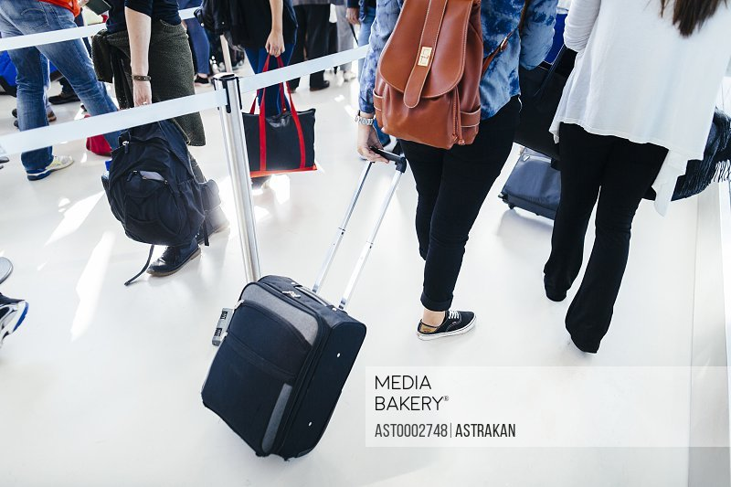 Rear view of businesswomen with luggage walking at airport