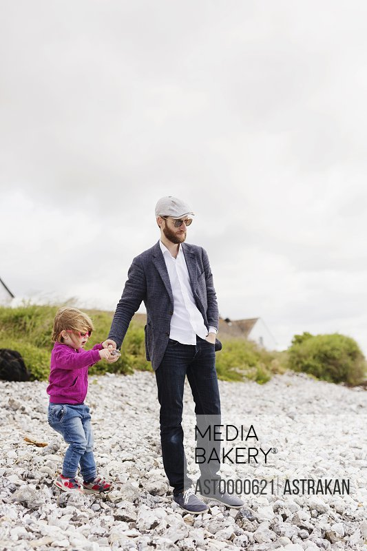 Father and daughter holding hands at beach against sky