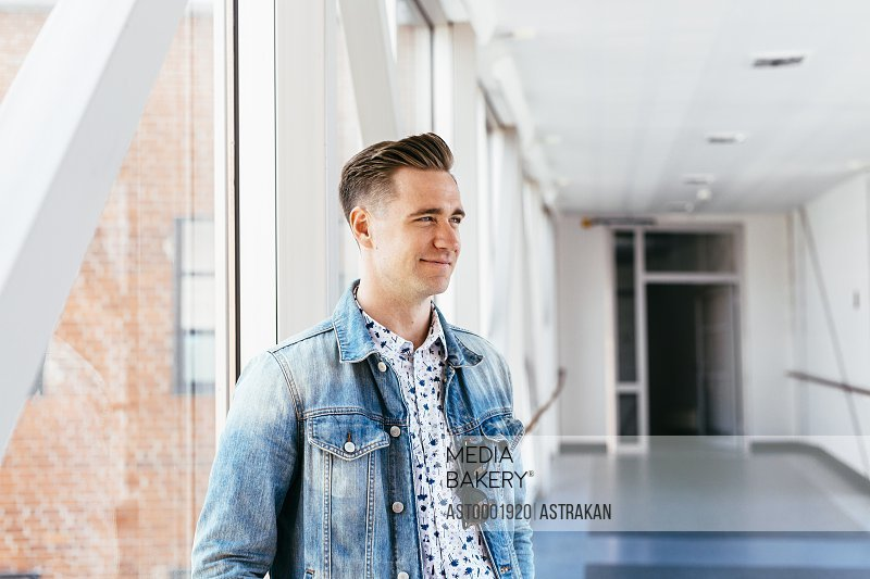 Smiling media student looking away while standing at passage in university