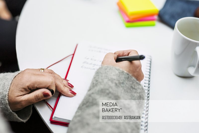 Cropped image of businesswoman writing in diary during business meeting