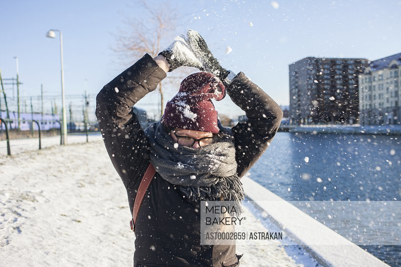 Woman playing with snow in city