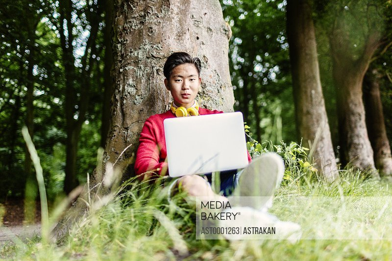 Portrait of male university student with laptop sitting at park