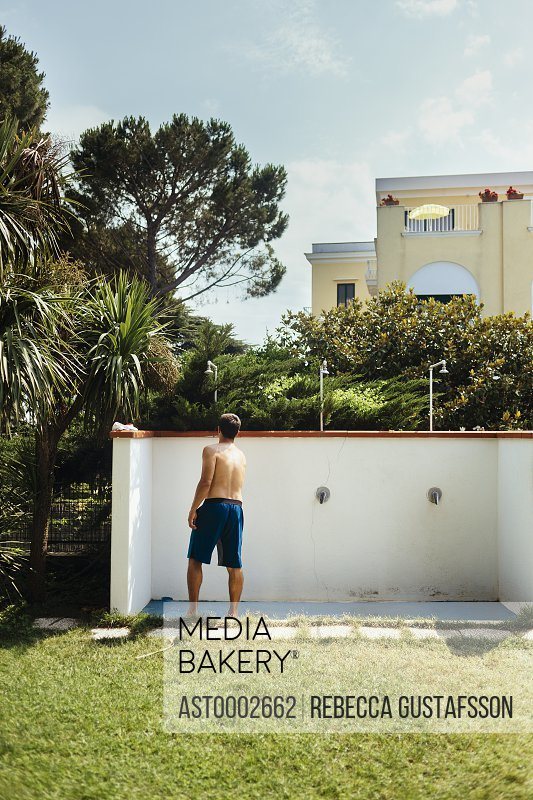 Rear view of man standing under shower in yard