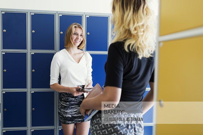 University female friends talking in locker room
