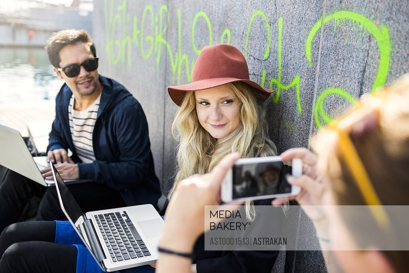 Cropped image of woman photographing freelancers sitting against wall