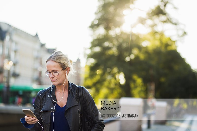 Mature woman looking at smart phone while waiting for friend at street