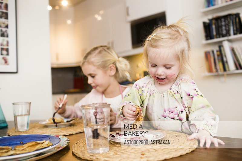 Cute girls eating pancakes on table at home