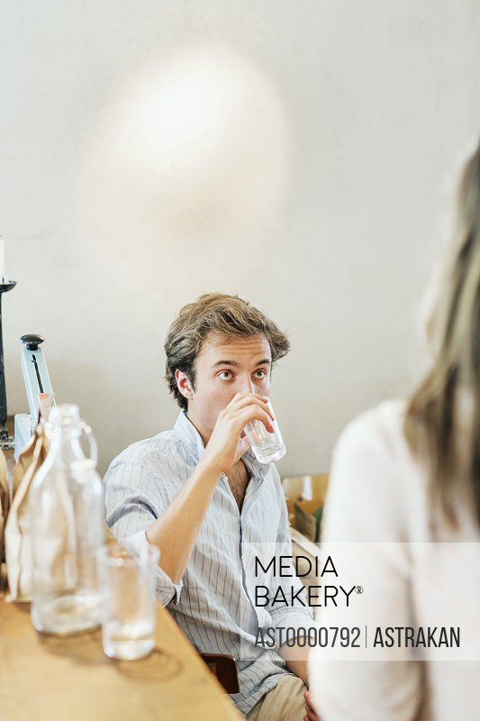 Young man drinking water while looking at woman in restaurant