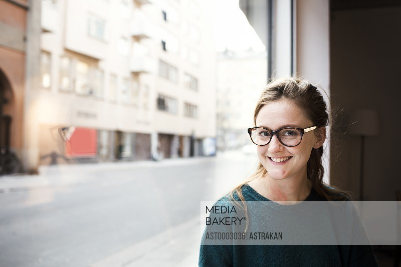 Portrait of mid adult businesswoman smiling by office window