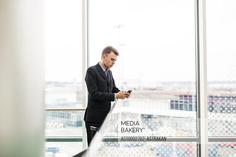 Businessman using smart phone in airport