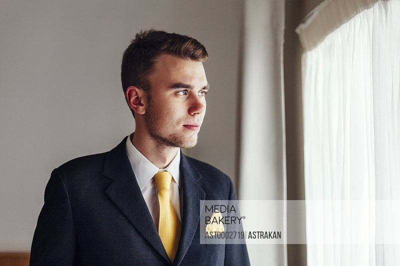 Thoughtful well-dressed businessman looking away in hotel room