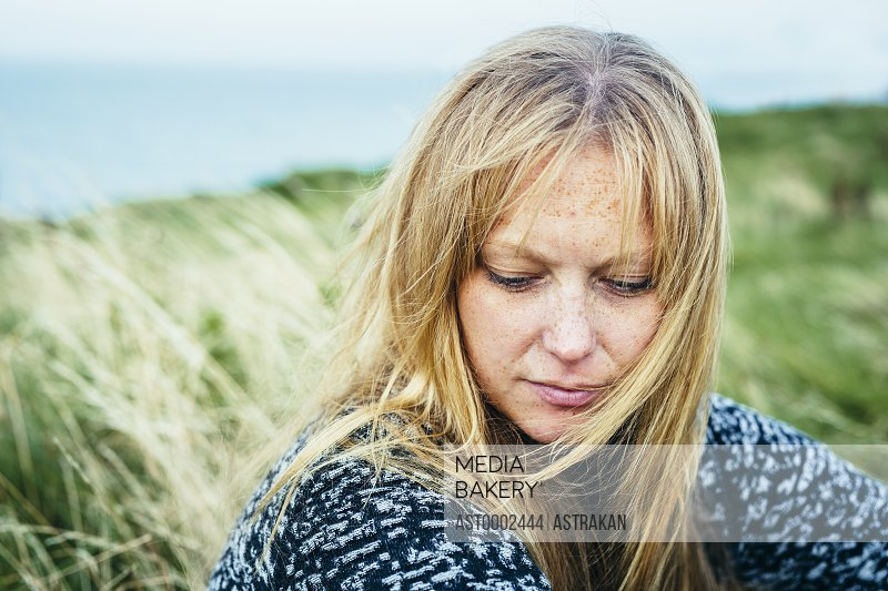 Close-up of thoughtful blond woman sitting on grassy field