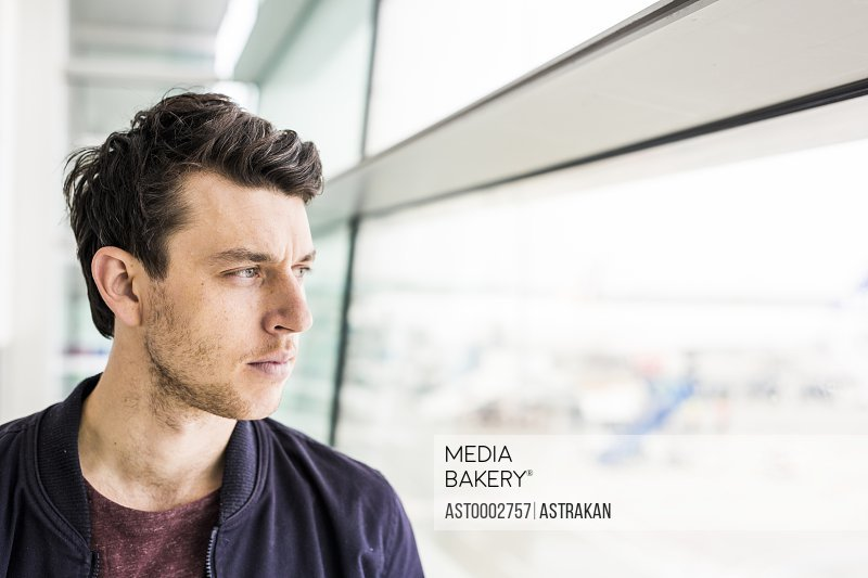 Thoughtful businessman looking through window at airport