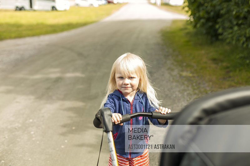 Portrait of girl with baby carriage on street