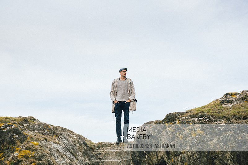 Man looking away while standing on cliff against sky