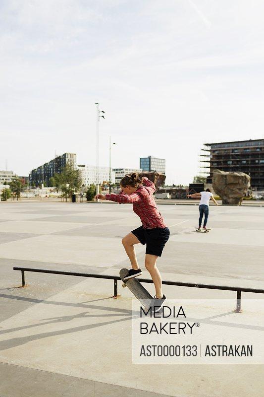 Full length of woman skateboarding on railing in skateboard park