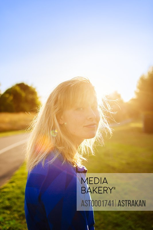 Side view portrait of female athlete at park during sunset