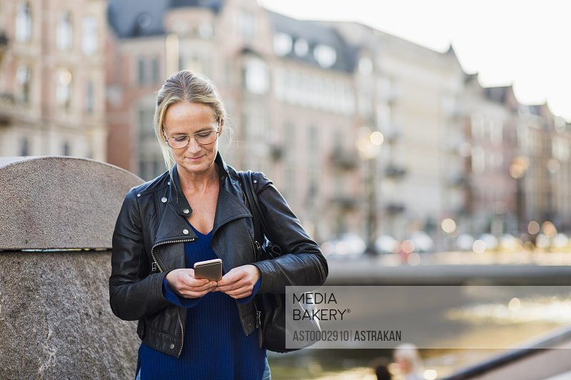 Mature woman using smart phone while standing on street against buildings