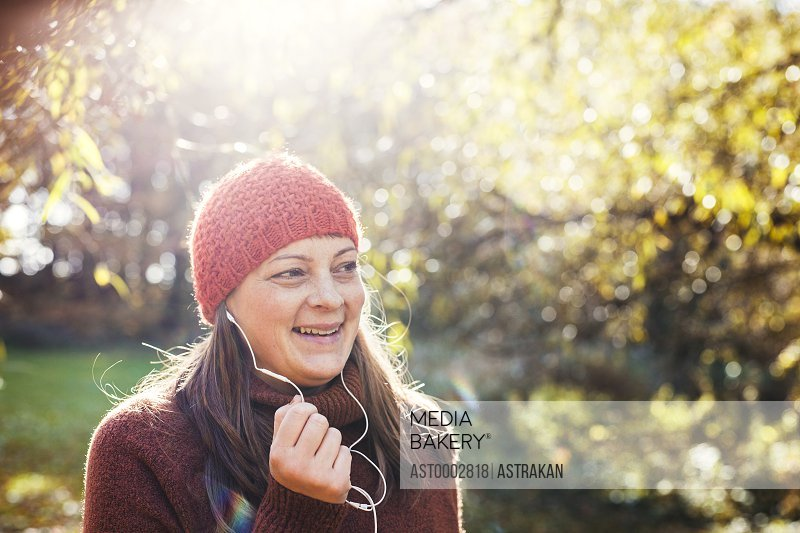 Happy mature woman listening music in forest