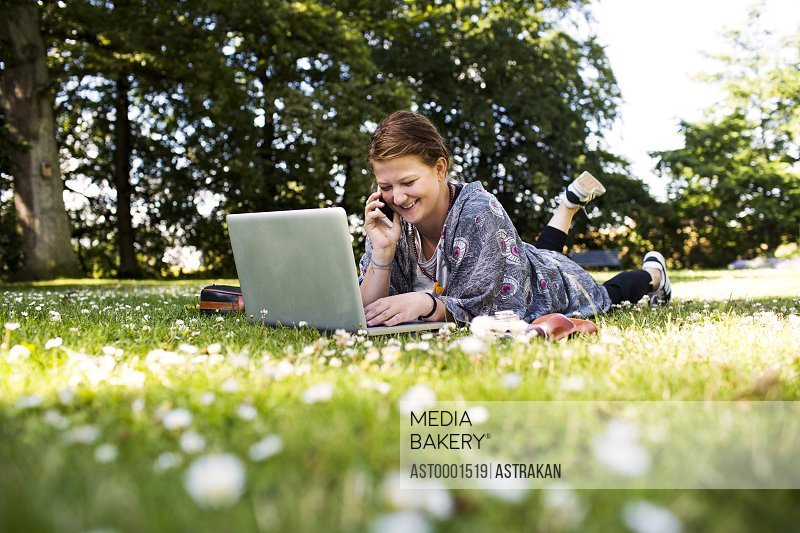 Happy woman talking on phone and using laptop at park