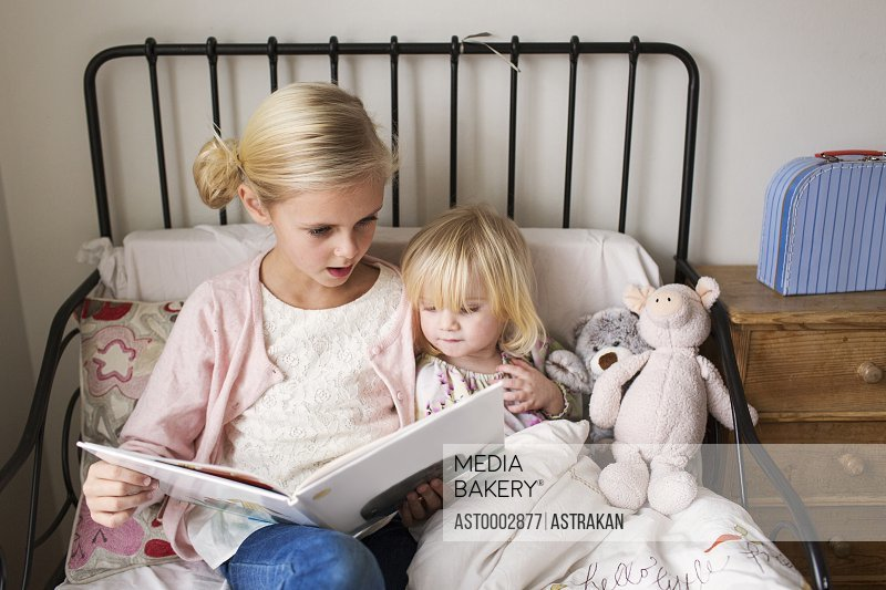 Girls reading book while relaxing on bed at home