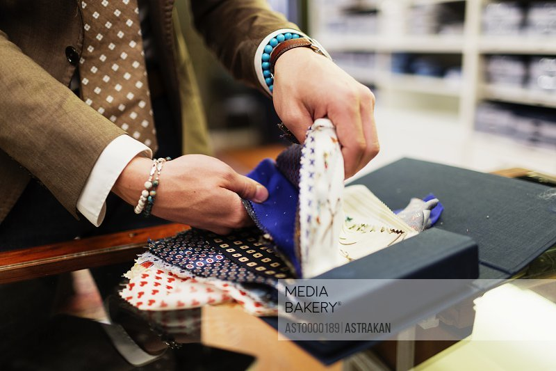 Midsection of fashion designer choosing from fabric swatch in clothing store