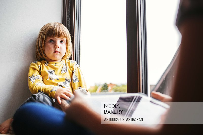 Portrait of cute girl sitting with sister using digital tablet on window sill