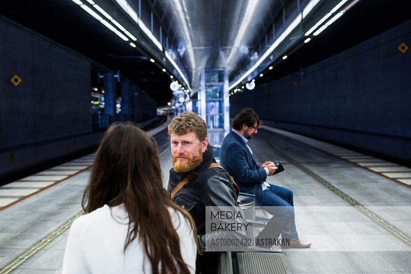 Business colleagues discussing while sitting at subway station