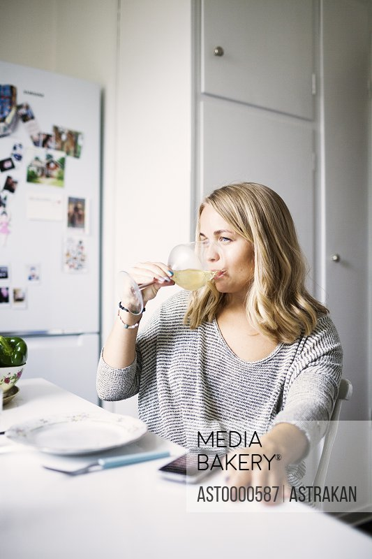 Young woman drinking wine at home