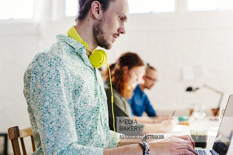 Young businessman using laptop with colleagues working in background at creative office