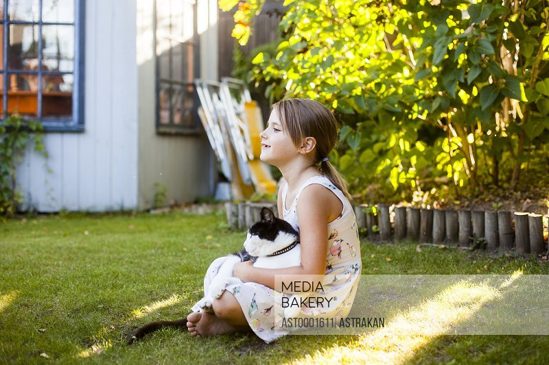 Full length side view of girl with cat sitting in backyard