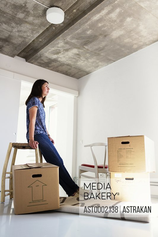 Full length side view of young woman in new house